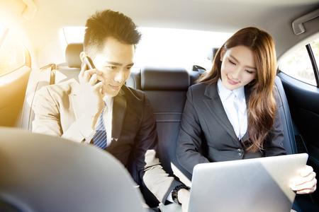L'homme d'affaires et femme travaillant ensemble dans la voiture