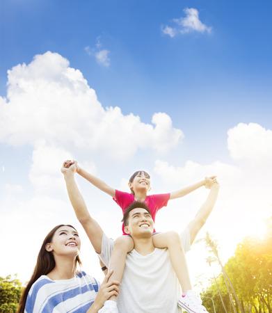 familias felices: Familia asi�tica feliz con el fondo de nubes