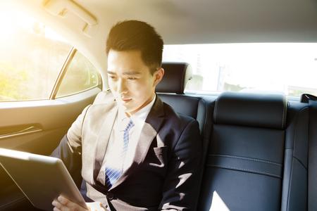 joven hombre de negocios que usa la PC de la tableta en el coche por la mañana