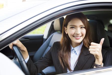 jonge vrouw zitten in de auto en het tonen van thumbs up