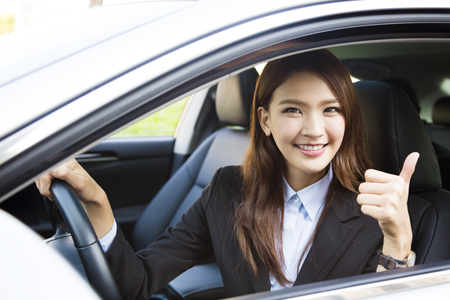 sell: young business woman sitting in car and showing thumbs up