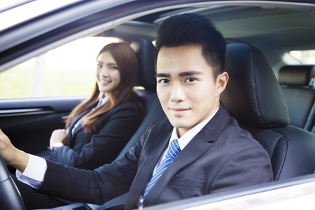 happy young business man and woman driving in the car