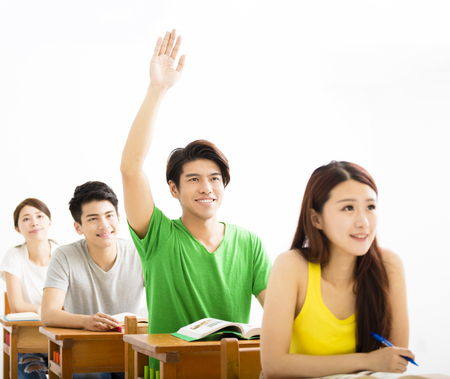 raise hand: college student raise hand for question in classroom