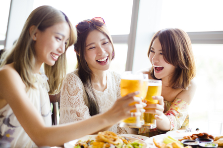 Groep meisjesvrienden roosteren en eten in het restaurant