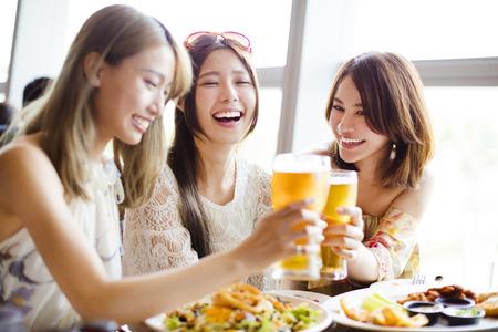 Gelukkige groep vriendinnen roosteren en eten in het restaurant Stockfoto