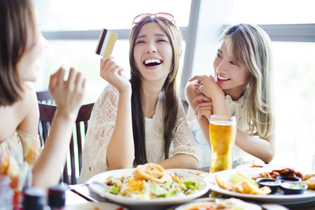 asia women: young group showing credit card and chatting in restaurant