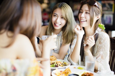chat: happy female friends sitting and chatting in restaurant