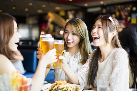 bebiendo vino: Feliz grupo de amigos de la chica tostar y comer en el restaurante Foto de archivo