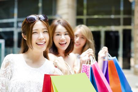 chicas de compras: joven grupo de mujeres que llevan bolsas de la compra en la calle