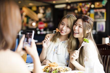 레스토랑에서 사진을 촬영 한 스마트 폰과 행복 친구