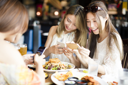 taking: happy friends with smart phones taking picture of food at restaurant