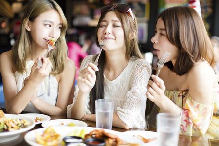 Mladá žena s přáteli si jídlo v restauraci
