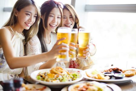 utazási: boldog csoport lány barátai pirítás és étkezés az étteremben