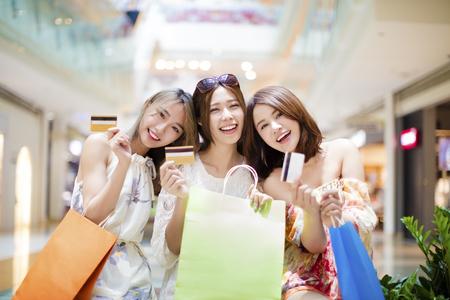 chicas compras: Las mujeres jóvenes grupo que muestra la tarjeta de crédito y bolsas de la compra