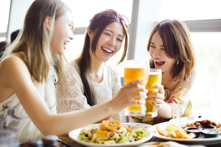 Groupe heureux d'amis fille grillage et de manger dans le restaurant