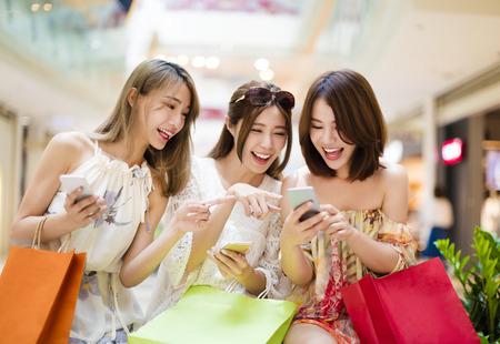 compras: mujer joven feliz mirando teléfono inteligente en el centro comercial