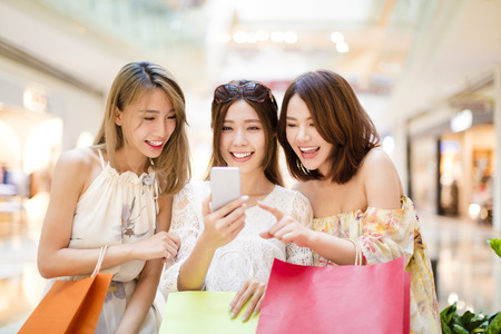 gelukkige jonge vrouw kijkt smart phone in winkelcentrum