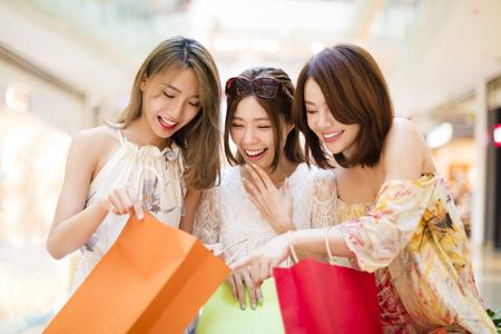 Überrascht junge Frauen, die die shooping Taschen suchen Standard-Bild
