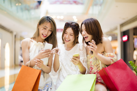 gelukkige jonge vrouw kijkt smart phone in winkelcentrum Stockfoto