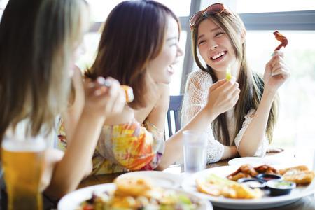 Jeune femme Amis Bénéficiant repas dans le restaurant Banque d'images - 57079611