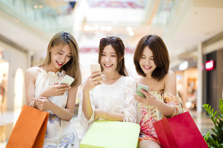 chatting: happy young woman  watching smart phone in shopping mall