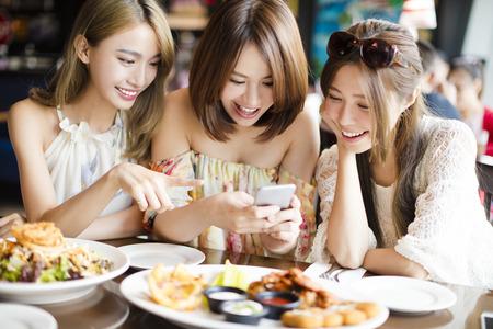 hablando por telefono: amigos felices con los tel�fonos inteligentes que toman el cuadro en el restaurante Foto de archivo