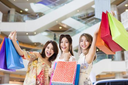 feliz grupo de mujeres que llevan bolsas de la compra en centro comercial