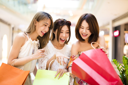 happy shopping: Surprised young women looking the shopping  bags