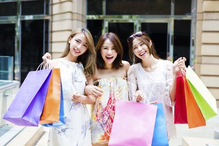 chicas compras: joven grupo de mujeres que llevan bolsas de la compra en la calle