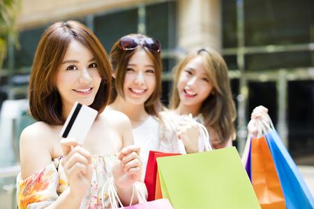 Feliz mujeres jóvenes, mostrando los bolsos de compras y tarjeta de crédito