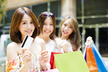 woman holding card: happy young Women showing Shopping Bags and credit card