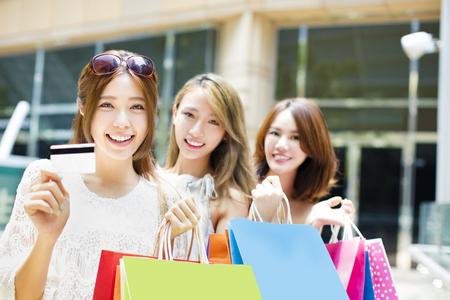 Happy jonge vrouwen die het winkelen zakken en creditcard Stockfoto