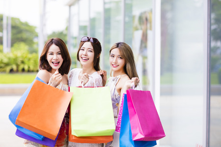 young Women group Carrying Shopping Bags On Street Stock Photo