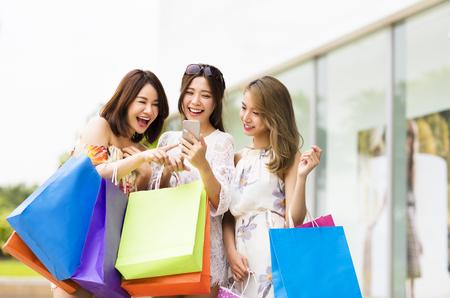 chicas compras: mujer joven feliz mirando teléfono inteligente en el centro comercial