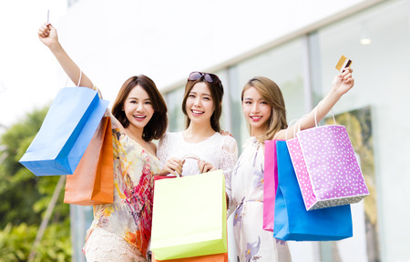 tarjeta de credito: Feliz mujeres jóvenes, mostrando los bolsos de compras y tarjeta de crédito