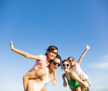 happy family having fun outdoors against blue sky background Archivio Fotografico