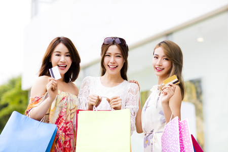 chicas de compras: Feliz mujeres jóvenes, mostrando los bolsos de compras y tarjeta de crédito