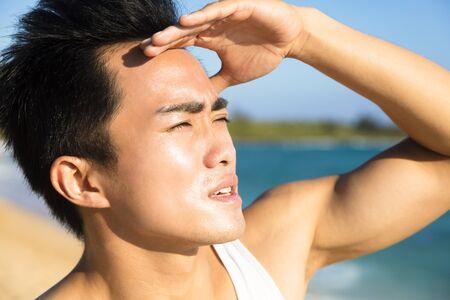 heat wave: closeup young man face under  summer heat wave