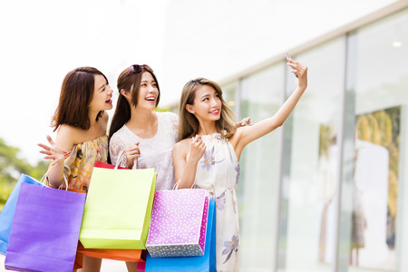 niñas chinas: felices jóvenes mujeres que toman autofotos mientras que las compras