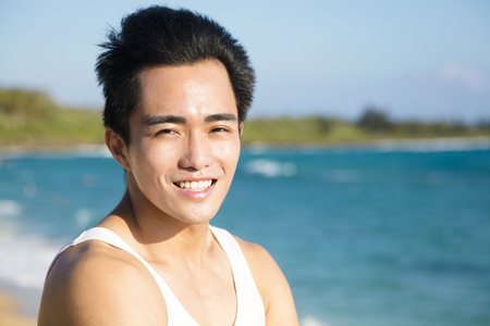 relaxing beach: smiling young man on the beach