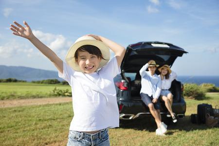 家族: 小さな女の子と幸せな家庭が車で旅行します。