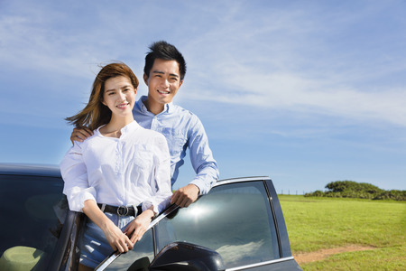 young couple standing near the car and enjoy summer vacation