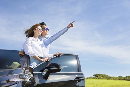 joven pareja de pie cerca del coche y disfrutar de las vacaciones de verano
