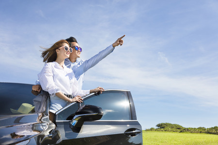 space travel: young couple standing near the car and enjoy summer vacation