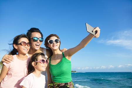 personas tomando agua: familia feliz teniendo una autofoto en la playa