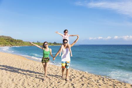 esposas: la familia feliz joven caminando por la playa Foto de archivo