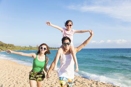 viaje familia: la familia feliz joven caminando por la playa Foto de archivo