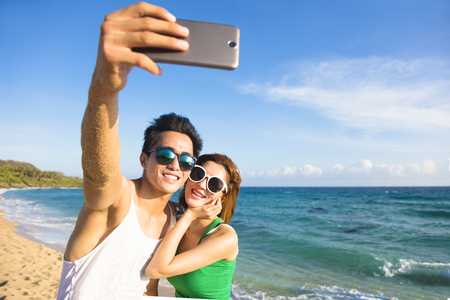 asian lifestyle: young couple  taking vacation selfie photograph at the beach