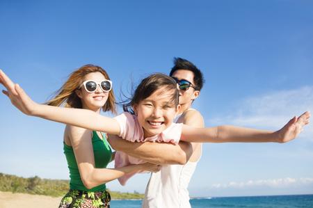 Счастливый молодой семьи, с удовольствием на пляже