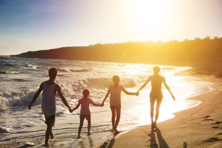 happy young family walking on beach at sunset
